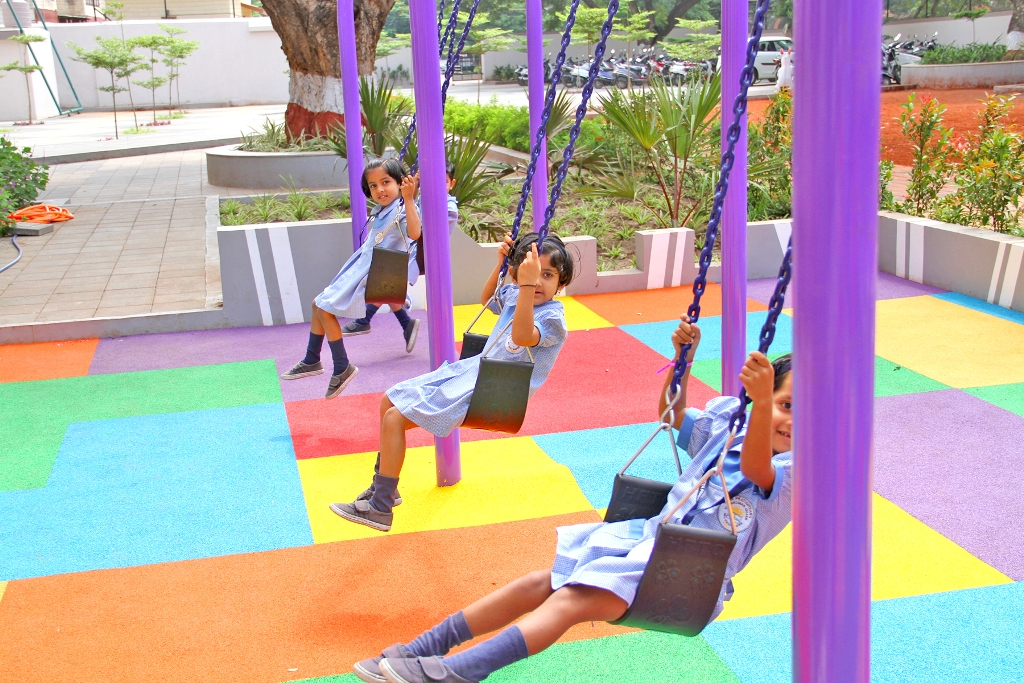 A Pretty Cheerful Little Kids are having fun on a Swing in a School Playground.