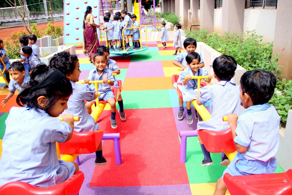 Little Kids of Pre-Primary playing on a Seesaw at School Playground.
