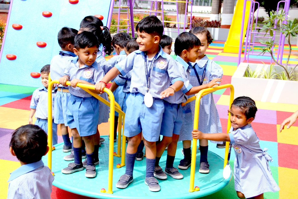Tiny Tots of Nursery Playing on Carousal at School Playground