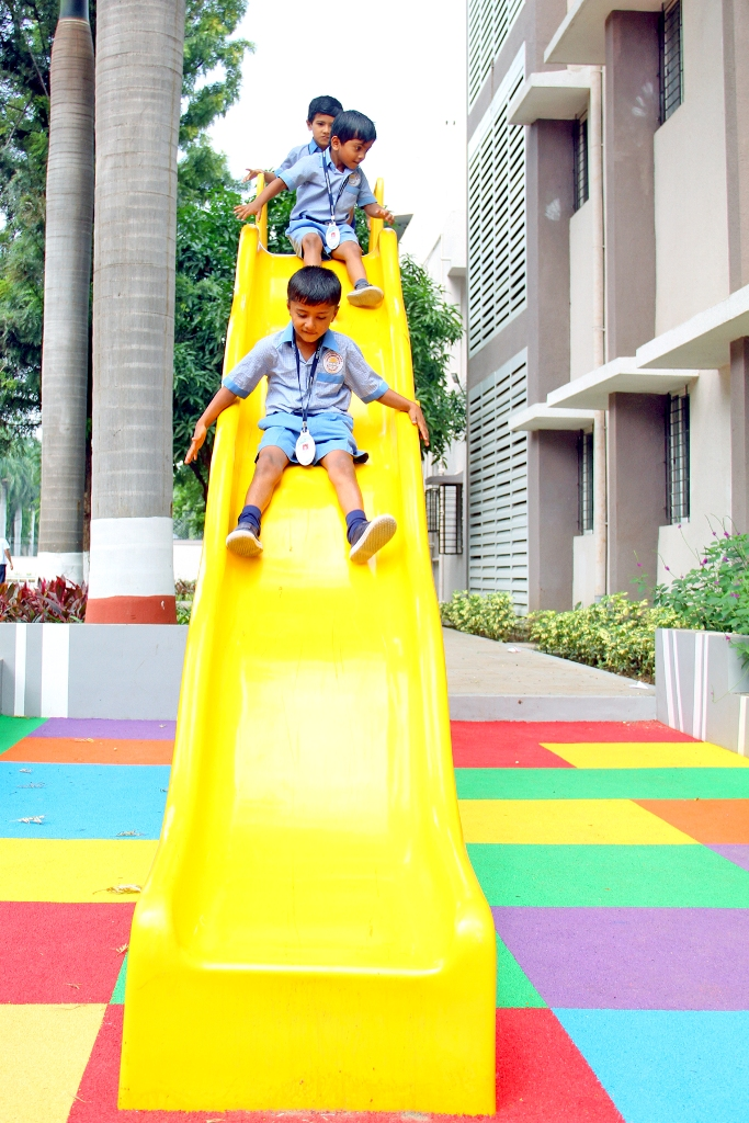 Pre-Primary Kids sliding joyfully in School Playground